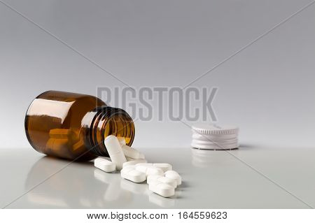 Brown glass pill bottle and white pills
