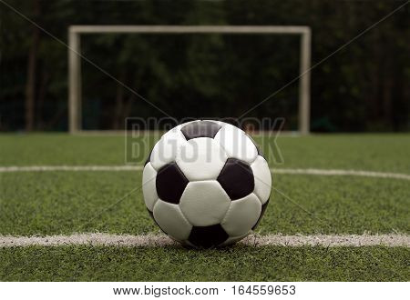Classic ball for playing soccer in white with black accents on artificial turf against gate, close-up view