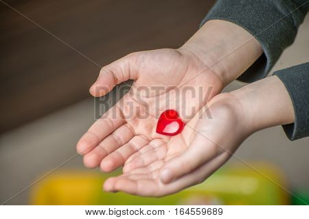 Close up of child hands holding a red heart