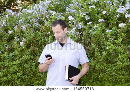 Man on his smart phone while holding a Bible.