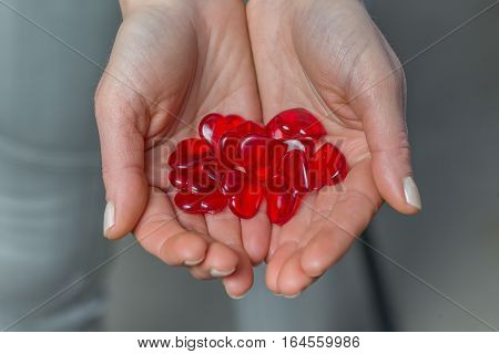 Close up of woman's hands holding red hearts.