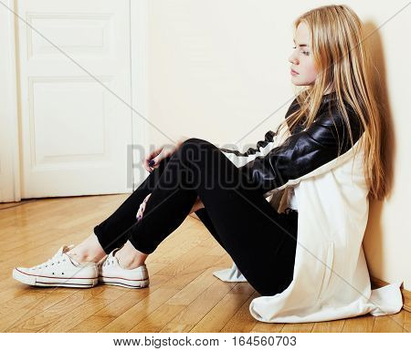 young pretty teenage blond girl sitting on floor at home despair sad alone, lifestyle concept close up