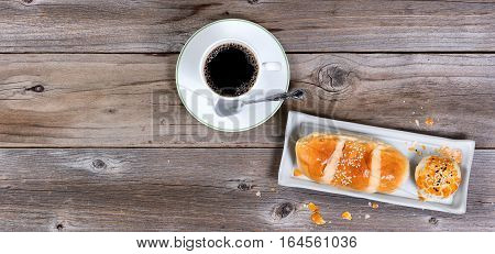 Freshly baked pastries with dark coffee on rustic wooden table. Flat layout with copy space.