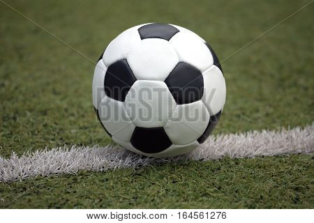 Classic ball for playing soccer in white with black accents on artificial turf line, close-up view