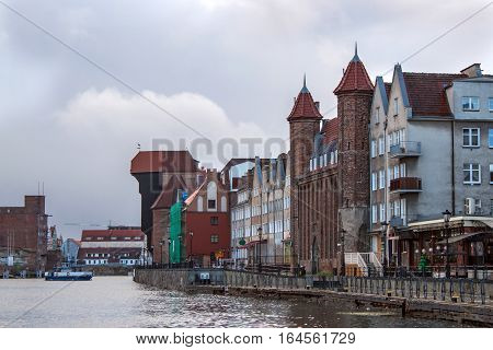 Panorama of historic part of town and the Motlawa River with its famous medieval Crane and Gate Straganiarska. Gdansk is a Polish city on the Baltic coast and popular center of tourism.