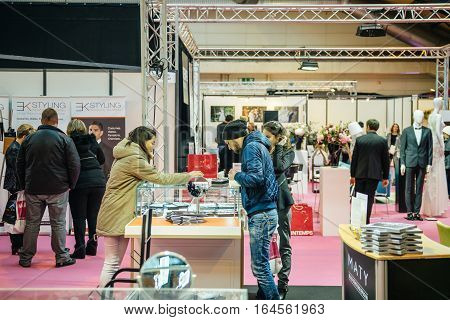 STRASBOURG FRANCE - JAN 8 2017: Beautiful young couple admiring wedding rings and engagements rings at Salon du Marriage the guide exhibition for bridal and formal wear industry
