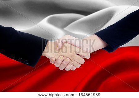 Photo of agreement handshake with two entrepreneur hands shaking hands with a Poland flag background