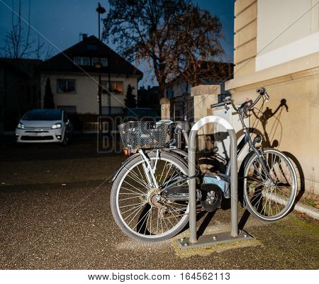 Bicycle parked in city at night secured with chain