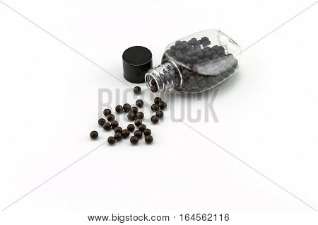 Black pills of traditional medicine or Black bolus near bottle stack on white background.