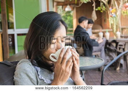Portrait Of Happy Asian Woman With Coffee Mug In Her Hands. Loving Coffee Concept.