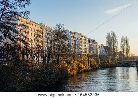 French apartment buildings alongside Ill river bankside on a calm winter day