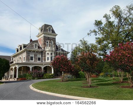The Cylburn Mansion House at Cylburn Arboretum in Baltimore Maryland with Crepe Myrtle trees and other flowering foliage in bloom on a summer day.
