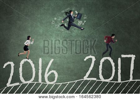Concept of business competition in 2017. Three Asian workers running and jumping to compete toward 2017