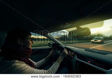 Woman driving on German autobahn at dusk taking care of the coming from the fron car security highway