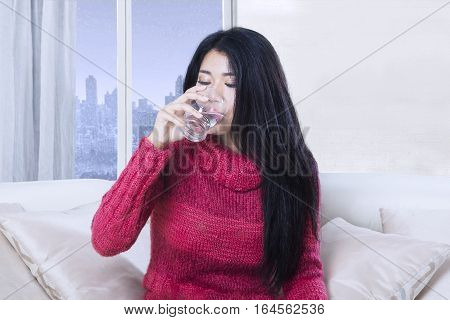 Portrait of beautiful woman drinks a glass of water while wearing warm clothes with winter background on the window