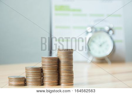 Concept business finance save money Coins stack on wood table with blurred calendar and alarm clock