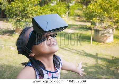 Adorable asian kid with virtual reality playing in a nature outdoors.