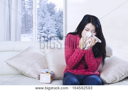 Portrait of beautiful woman sneezing in tissue while sitting on the couch with winter background on the window