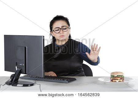 Image of an attractive businesswoman wearing glasses and refusing cheeseburger with a computer on the desk