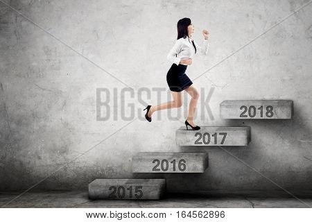 Picture of young businesswoman stepping on the stairs with number 2017 toward 2018