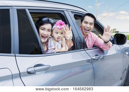 Cheerful Asian family sitting in the car looking out windows and waving hands together