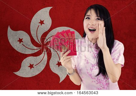 Image of young woman celebrate Chinese new year and wearing cheongsam dress while holding red envelope with flag of Hong Kong