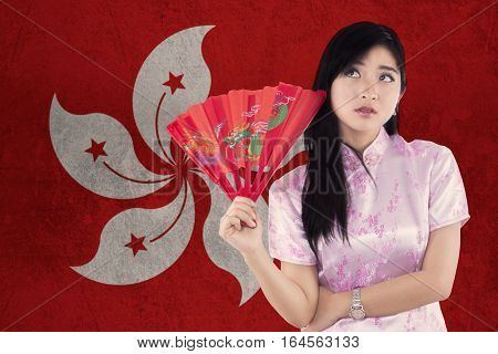 Image of pretty Chinese girl thinking idea while holding a fan and wearing cheongsam dress with Hongkong flag background