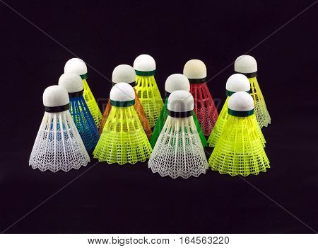 Many color badminton shuttlecocks with white corks isolated on black background