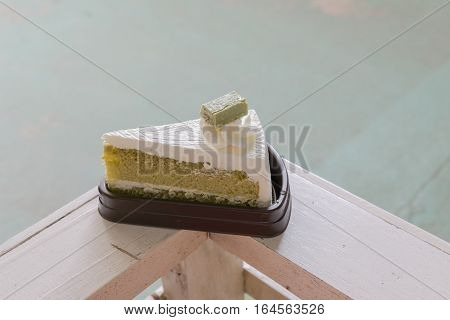 Matcha Cake Is Placed On A Wooden Fence.