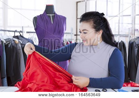 Portrait of a beautiful female designer is measuring textile material with measuring tool in the workplace
