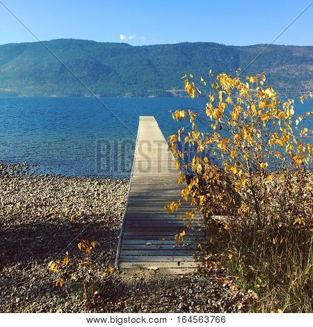 Lake landscape in autumn with wooden pier and bushes on rocky beach. Mountains and clear blue sky background. Sunshine and shadows on shore