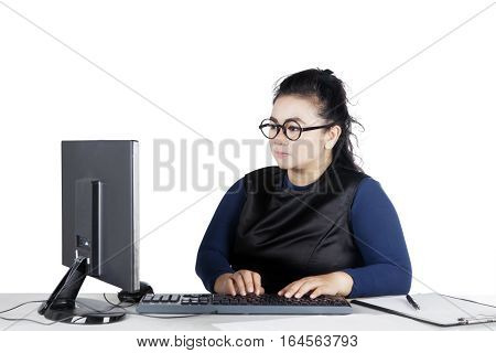 Portrait of fat woman typing on keyboard while sitting in front of her computer isolated on white background