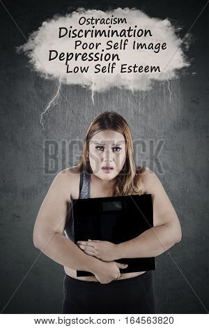 Portrait of a fat woman holding a weighing scale and looks frustrated thinking her problems