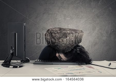 Picture of frustrated businesswoman sleeping on the desk with heavy stone over her head