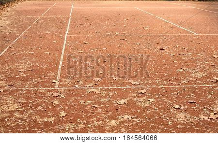 End of summer sport season. Empty tennis court with lot of yellow leaves in autumn