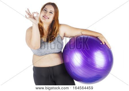 Image of obese female showing ok sign and smiling at the camera while holding a purple fit ball in the studio