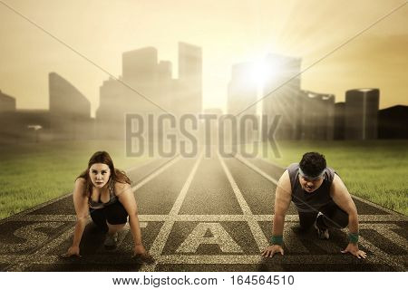 Portrait of overweight people kneel on the start line while ready to compete and try to chase their dream