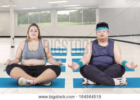 Picture of obese woman and her partner sitting on a mattress while meditating in a lotus yoga position