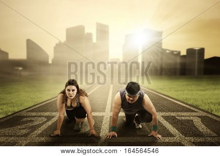 Image of overweight people ready to compete and try to chase their dream with numbers 2017 on the running track