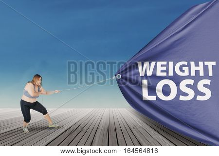 Overweight woman with blonde hair wearing sportswear and pulling a big flag with text of weight loss