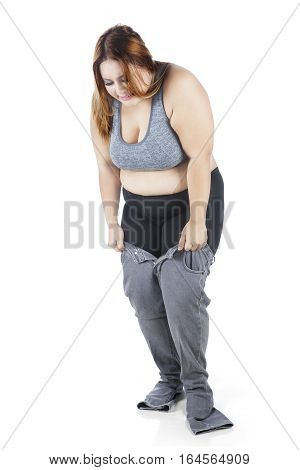 Image of overweight young woman tries to wear her old jeans in the studio