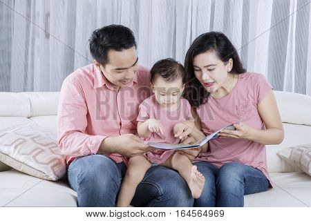Portrait of two Asian parents holding a book and reading a story tale on the couch with their baby