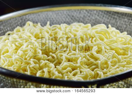 boiled instant noodle on circle stainless colander