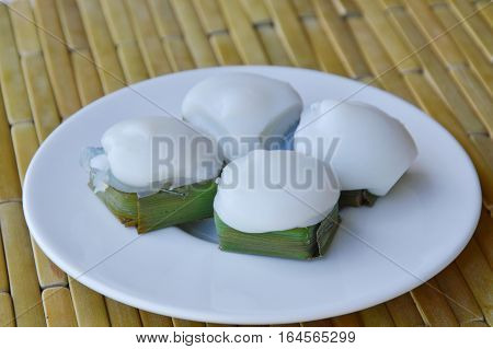 Thai pudding filling taro and topping coconut cream in banana leaf