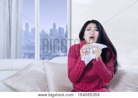 Portrait of sick woman holding a tissue in her hands while sneezing on the sofa