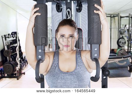 Portrait of strong overweight woman looking at the camera while workout on a shoulder press machine in the fitness center
