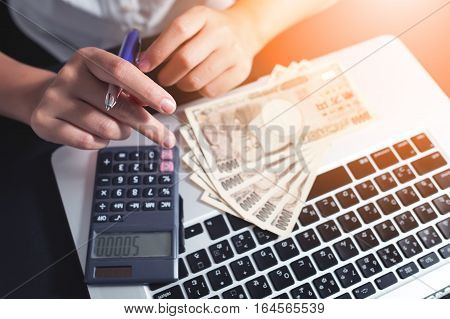 Female calculate Japanese bank on laptop. Savings, Finance, Economy and earning concept
