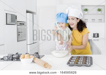 Young Asian mother and her little daughter making cake in the kitchen shot at home
