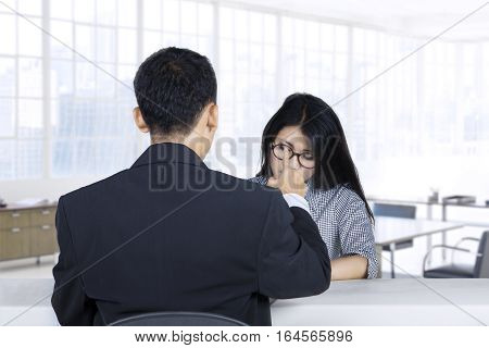 Portrait of a young woman looking down after rejected by recruiter in a job interview
