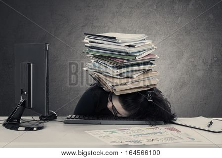 Frustrated woman sleeping on the desk with stack of documents over her head